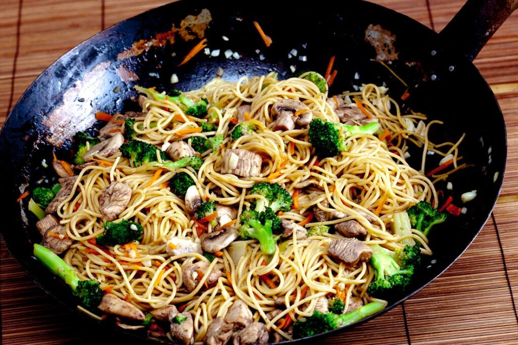 chicken chow mein with vegetables in a wok