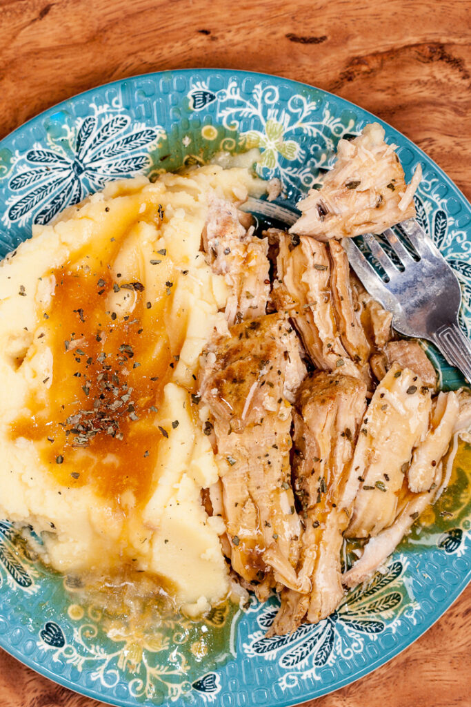 slow cooker pork loin with mashed potatoes on a plate