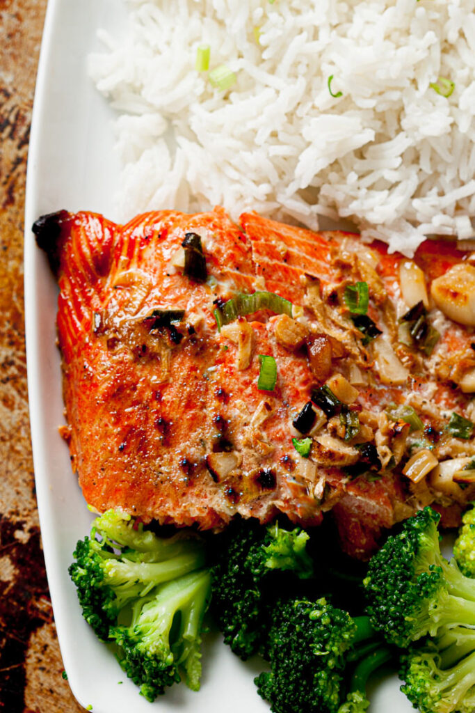 oven baked salmon with ginger soy marinade on plate with rice and broccoli