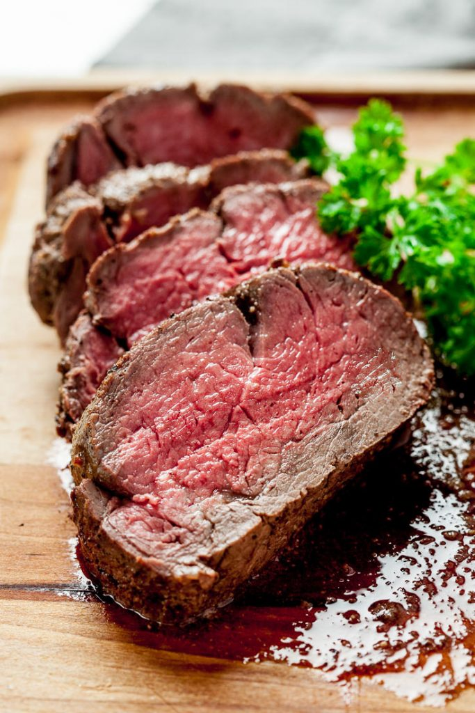 sliced beef tenderloin roast on cutting board
