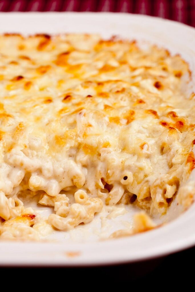 baked macaroni and cheese in white dish vertical