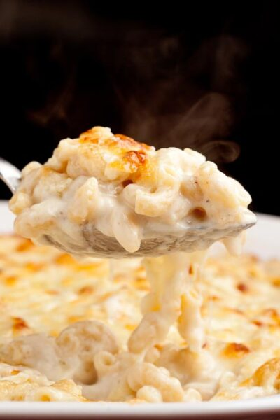 homemade macaroni and cheese with serving spoon in dish square