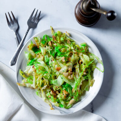 Stir Fry Cabbage with Olive oil and garlic on white plate with forks
