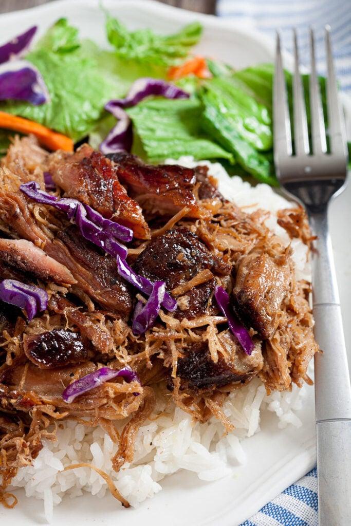 Kalua Pork shredded over rice on plate