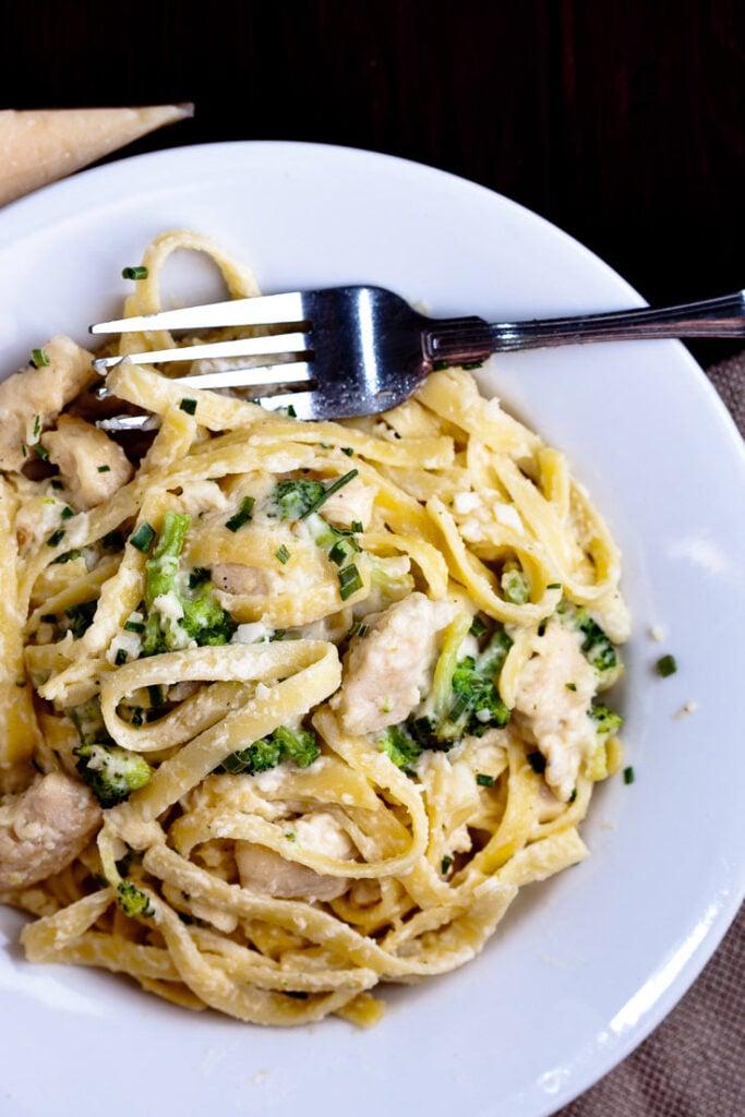 fettuccini alfredo with chicken and broccoli in white plate